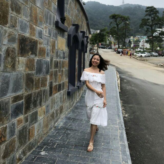Váy trắng dáng xòe dài,hở vai, thêu hoa nhí trên ngực và dưới chân váy làm điểm nhấn. Phù hợp đi biển hoặc đi dạo.